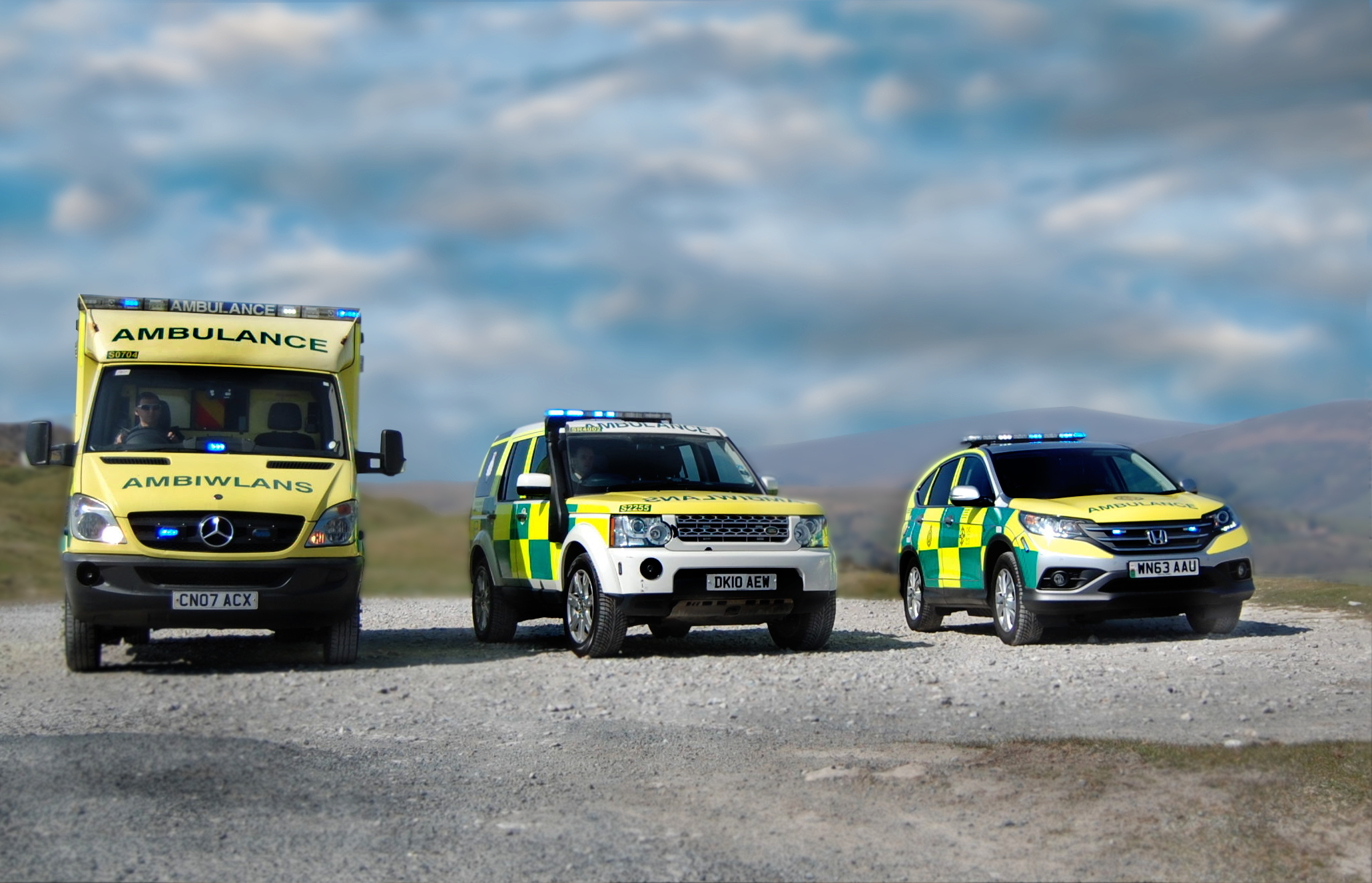 3 different types of ambulance vehicles parked top of a hill / 3 math gwahanol o gerbyd ambiwlans wedi'u parcio ar ben bryn